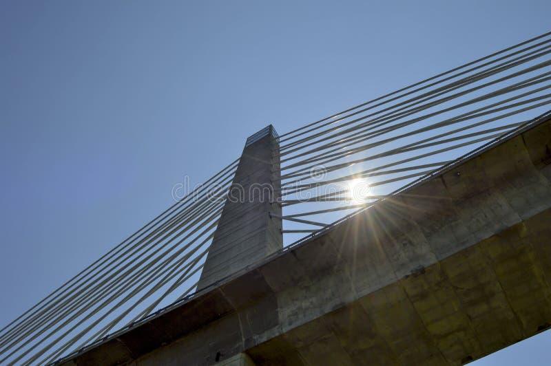 Sun dietro i cavi della guglia e di sostegno del ponte fotografie stock libere da diritti