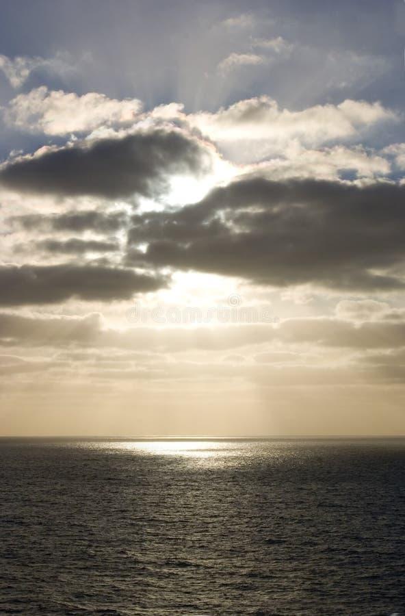 Sun dietro le nubi in mare fotografie stock libere da diritti