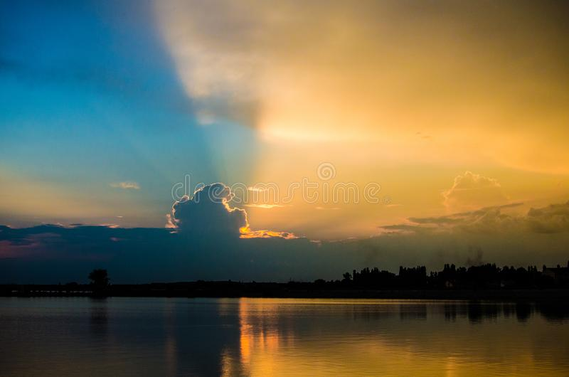 Sun dietro le nuvole che stabiliscono sopra un lago fotografia stock