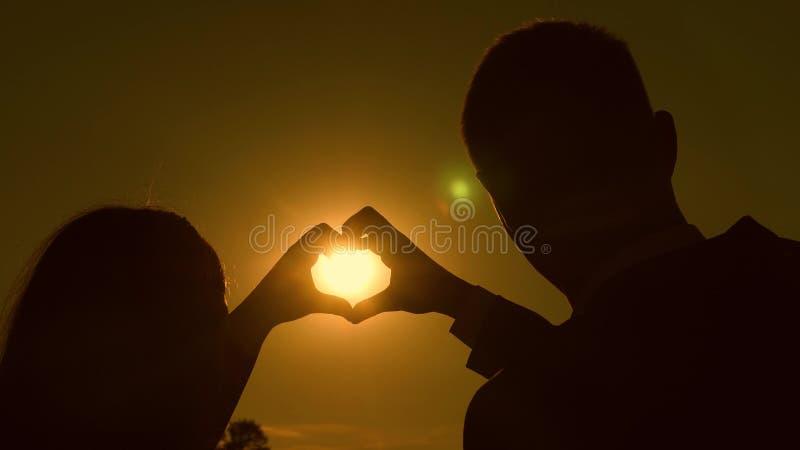 Sun a disposizione Lavoro di squadra di una coppia amorosa la coppia nell'amore mostra il simbolo del cuore con le mani Sposa e s immagini stock libere da diritti