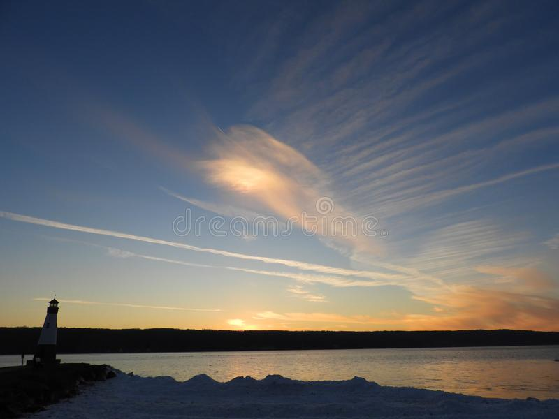 Sunset sky in winter over north west view of Cayuga Lake. East shoreline of Myers Park on Cayuga Lake in Lansing NY. Sky is illuminated by the setting sun across royalty free stock photo