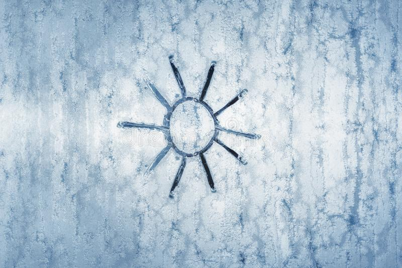 Sun drawing on a frozen window. Winter background. Frozen glass with sun sketch on it. Winter cold background. Ice on window. Christmas backdrop. December stock images