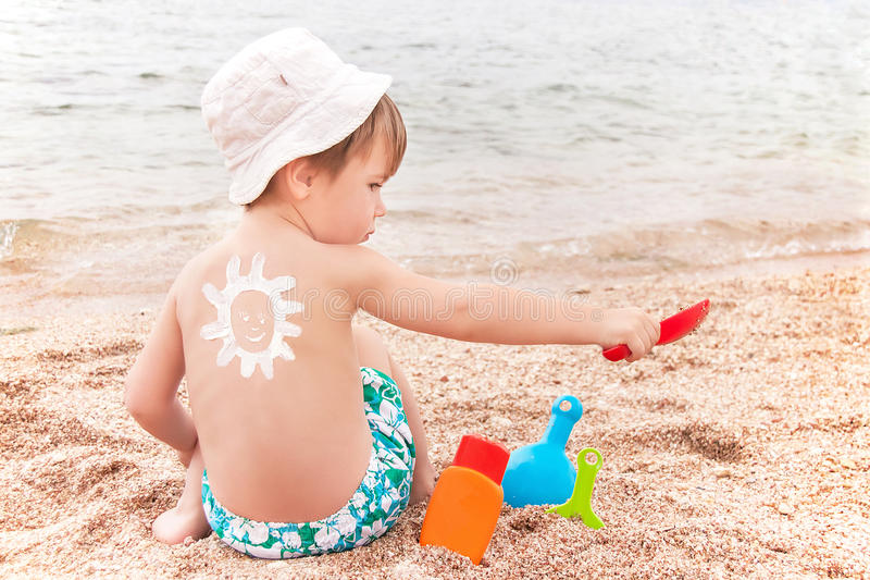 The sun drawing sunscreen on baby (boy) back. The sun drawing sunscreen (suntan lotion) on baby (boy) back. Caucasian child is sitting with plastic container of royalty free stock photography