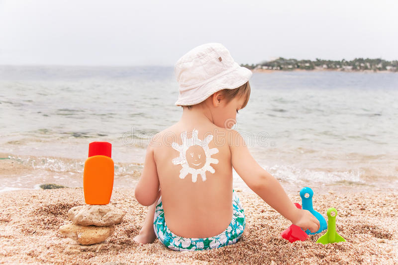 The sun drawing sunscreen on baby (boy) back. The sun drawing sunscreen (suntan lotion) on baby (boy) back. Caucasian child is sitting with plastic container of stock images