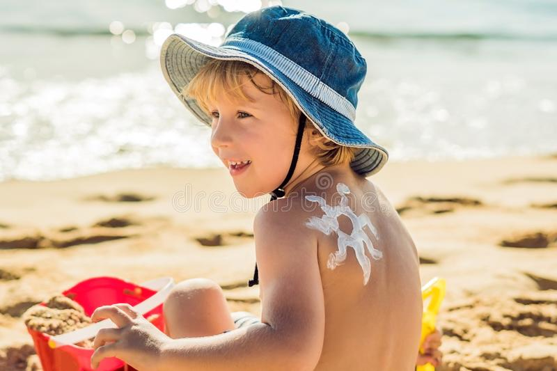 The sun drawing sunscreen ,suntan lotion on baby boy back. Caucasian child is sitting with plastic container of sunscreen and toys. On sunny beach. Close up stock images