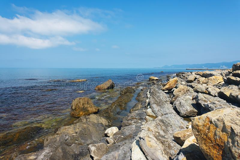 Sun-drenched rocky coast of the sea under blue sky royalty free stock image