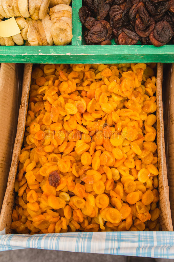 Sun-dried apricots peaches in basket, dried fruits on street market stock image