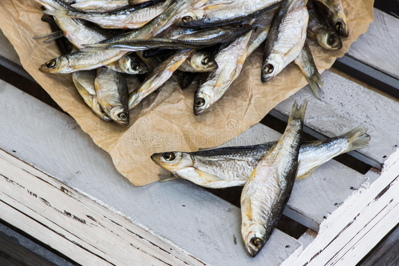 Sun dried salty fish. Stock-fish on the crate. royalty free stock images