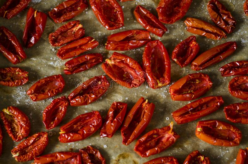 sun dried tomatoes in the cooking process with olive oil, spices basil, oregano, sea salt. delicacy, appetizer from Italy. royalty free stock photo