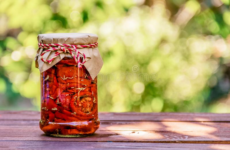 Sun dried tomatoes in glass jar on wooden table. Delicious gift. Vegetarian food. stock image