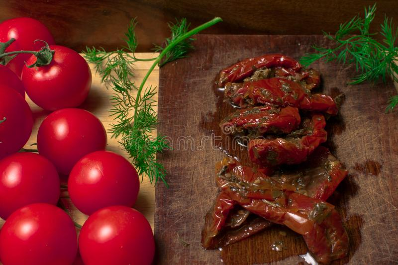 A lot of sun dried tomatoes. Sun dried tomatoes with herbs and dill, fresh organic tomatoes on wood royalty free stock photography