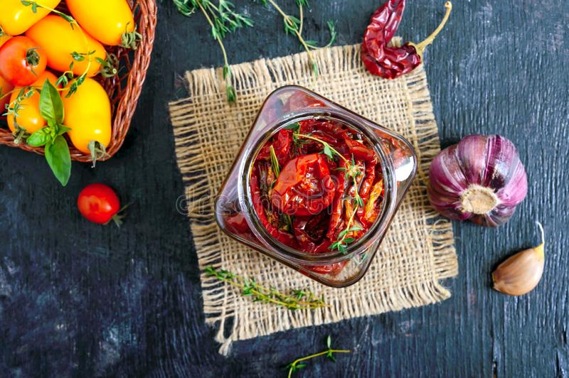 Sun-dried tomatoes with herbs, garlic in olive oil in a glass jar. Top view, flat lay royalty free stock image