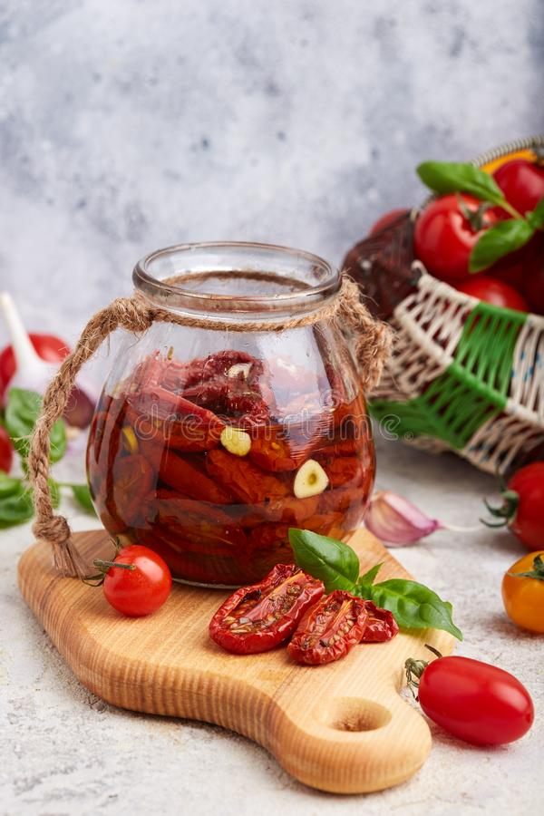 Sun dried tomatoes with herbs, garlic and olive oil in jar stock images