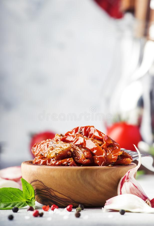 Sun dried tomatoes in olive oil with green basil and spices in wooden bowl on gray kitchen table, place for text royalty free stock photos