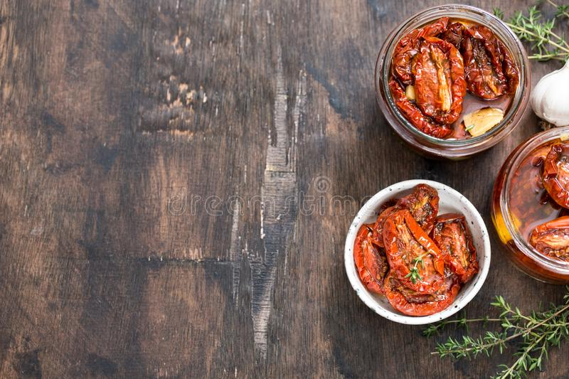 Sun dried tomatoes with olive oil in a jar on wooden background stock photography