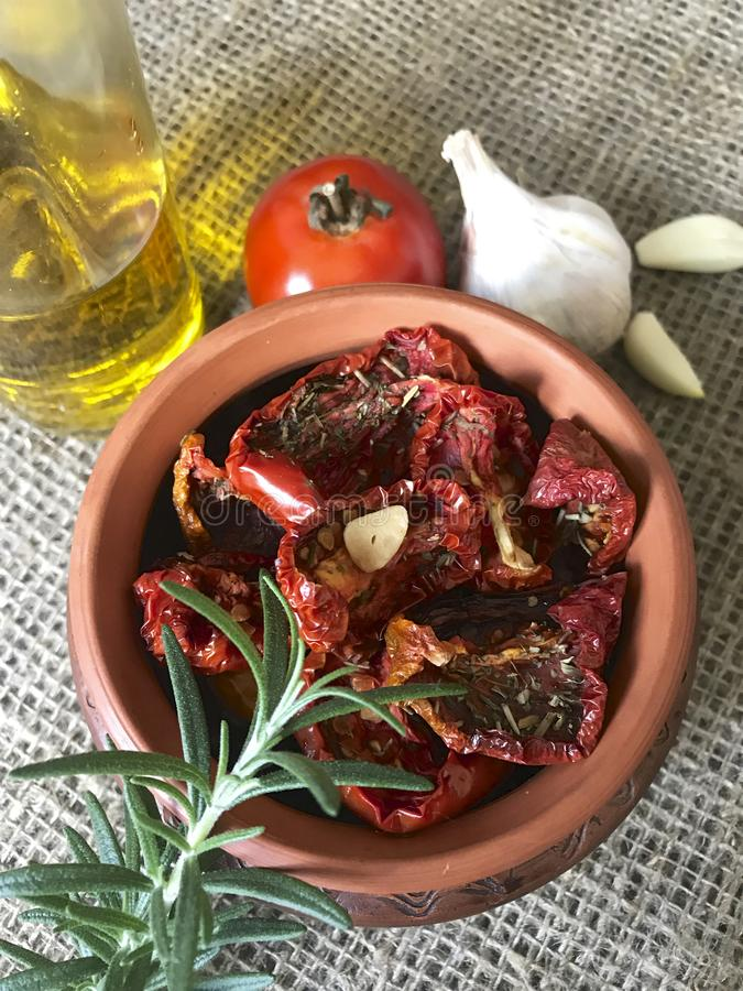 Sun-dried tomatoes with spices and garlic in a clay pot. Nearby is a bottle with olive oil, tomatoes, rosemary and garlic stock photos