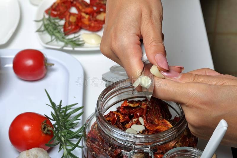 Sun-dried tomatoes with spices and garlic in a jar. Woman adds garlic. Near rosemary, tomatoes and garlic royalty free stock image