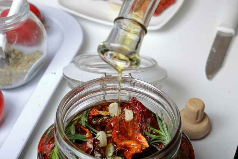 Sun-dried tomatoes with spices and garlic in a jar. Woman adds olive oil. Near rosemary, tomatoes and garlic stock image