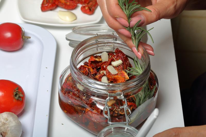 Sun-dried tomatoes with spices and garlic in a jar. Woman adds rosemary. Near rosemary, tomatoes and garlic stock photo