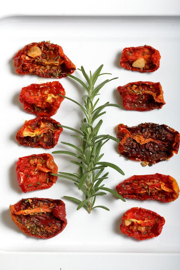 Sun-dried tomatoes with spices and garlic on a light tray. Nearby lies fresh rosemary.  royalty free stock images