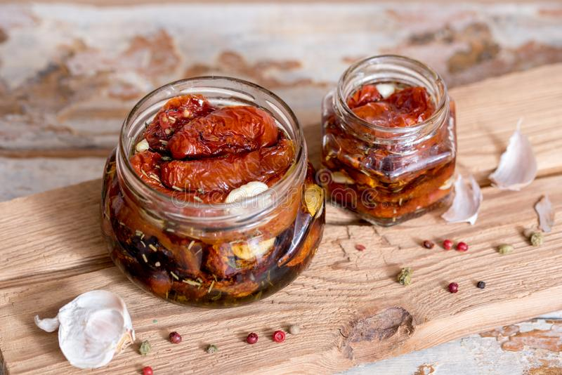 Sun dried tomatoes with thyme and sea salt in an olive oil in a glass jar on the old wooden background. Selective focus. stock photos