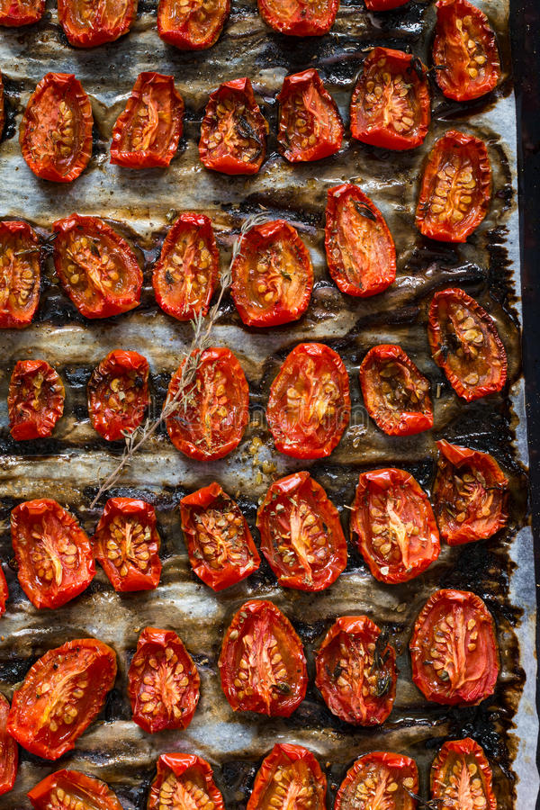 Sun dried tomatoes on a tray. Dried tomatoes pattern - Homemade dried tomatoes with thyme, sea salt and olive oil on a tray stock photo