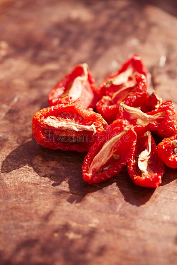 Sun-dried tomatoes on vintage wood royalty free stock photography