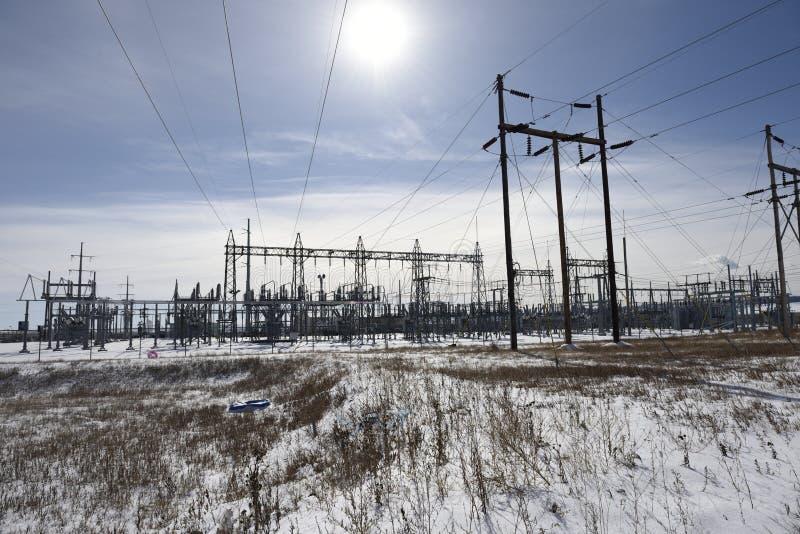 Sun e neve con le linee elettriche ad alta tensione e la sotto costruzione metallica della stazione di corrente elettrica immagini stock libere da diritti