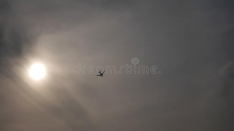 The Sun e silhueta de um voo do avião no céu nebuloso imagem de stock