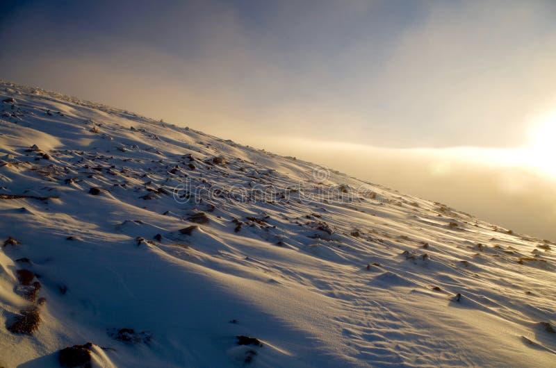 Sun en una montaña escocesa nevosa foto de archivo libre de regalías