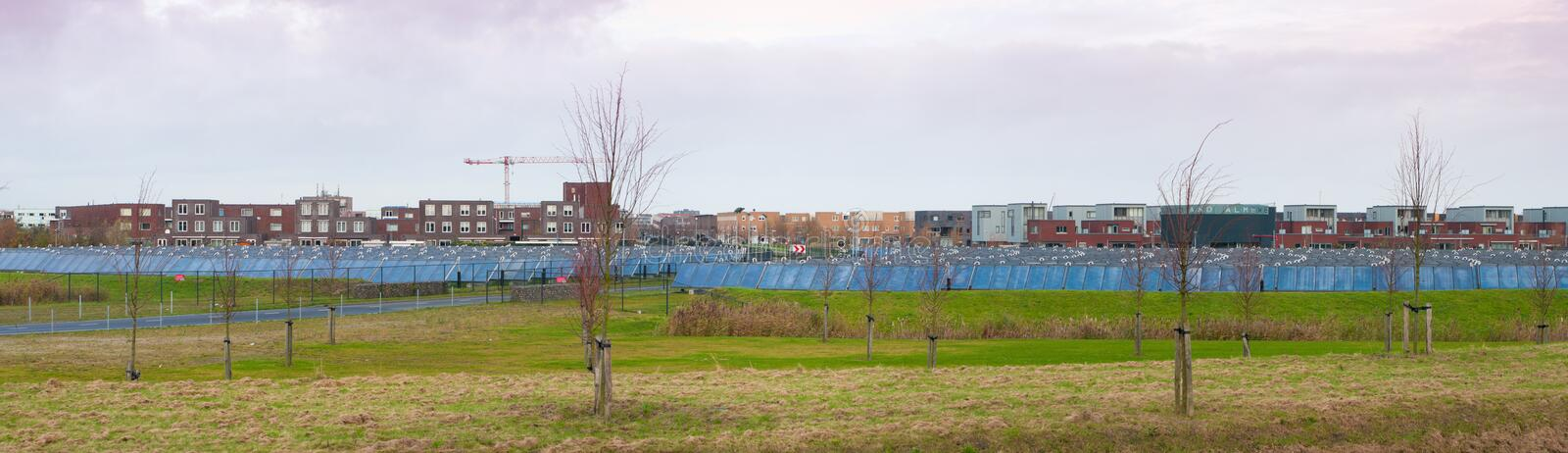 Sun energy. Area filled with solar collectors in Almere, Netherlands, providing energy for the residential area in the background royalty free stock photos