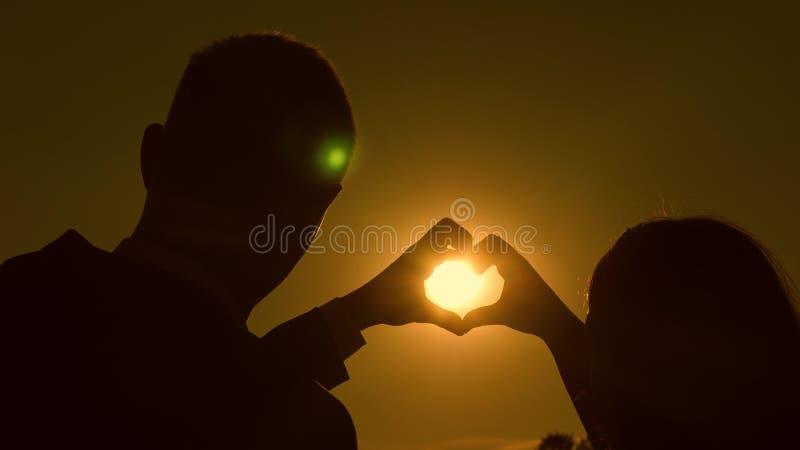 Sun está nas mãos Uma menina e seu noivo que fazem uma forma do coração pelas mãos oposto a um por do sol bonito no fotos de stock royalty free