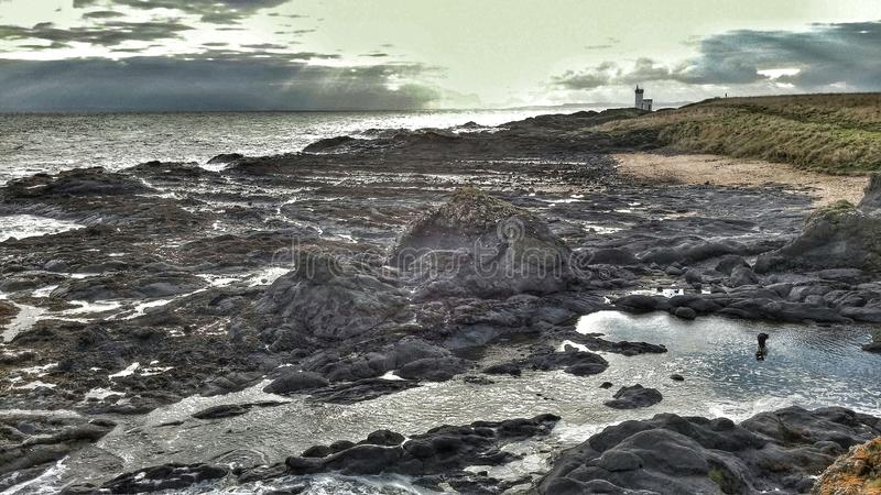 Sun estourou através da praia da rocha fotografia de stock