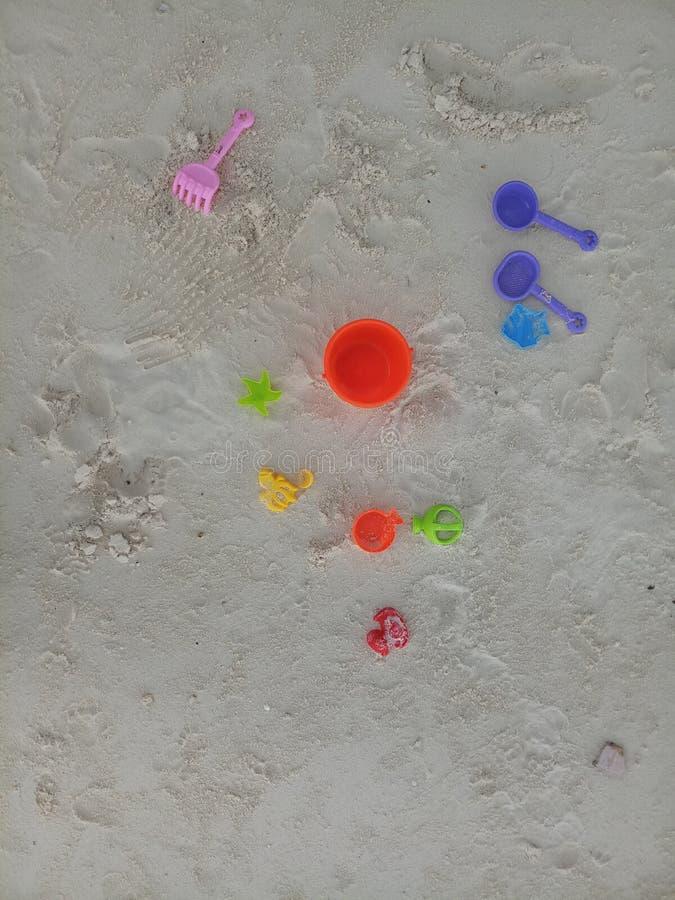 Sun et envoyer Child's jouant la ligne de jouets sur le sable de plage Maldive photos stock