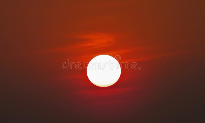 The sun is in the evening sky. Red and orange in color stock image