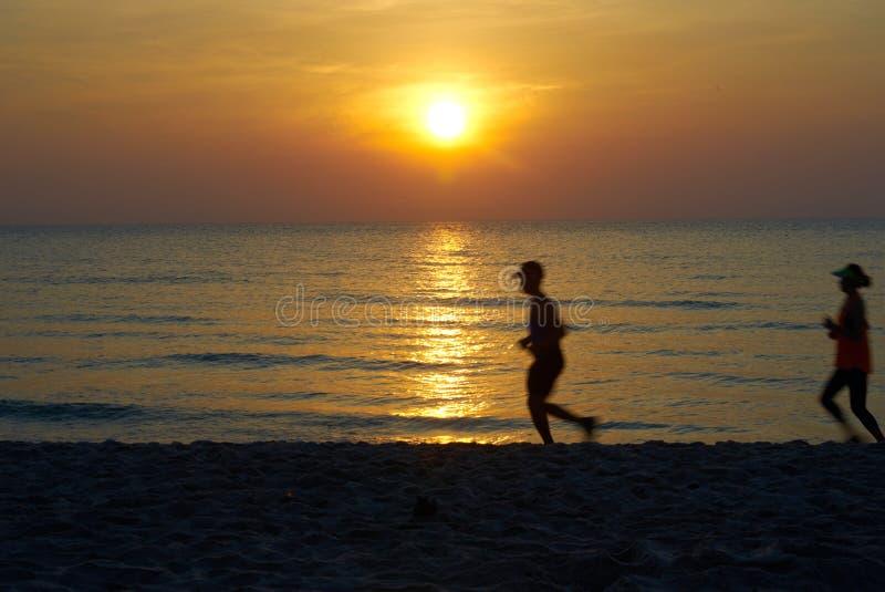 Sun fijó en la playa con la silueta corriente de la gente foto de archivo libre de regalías