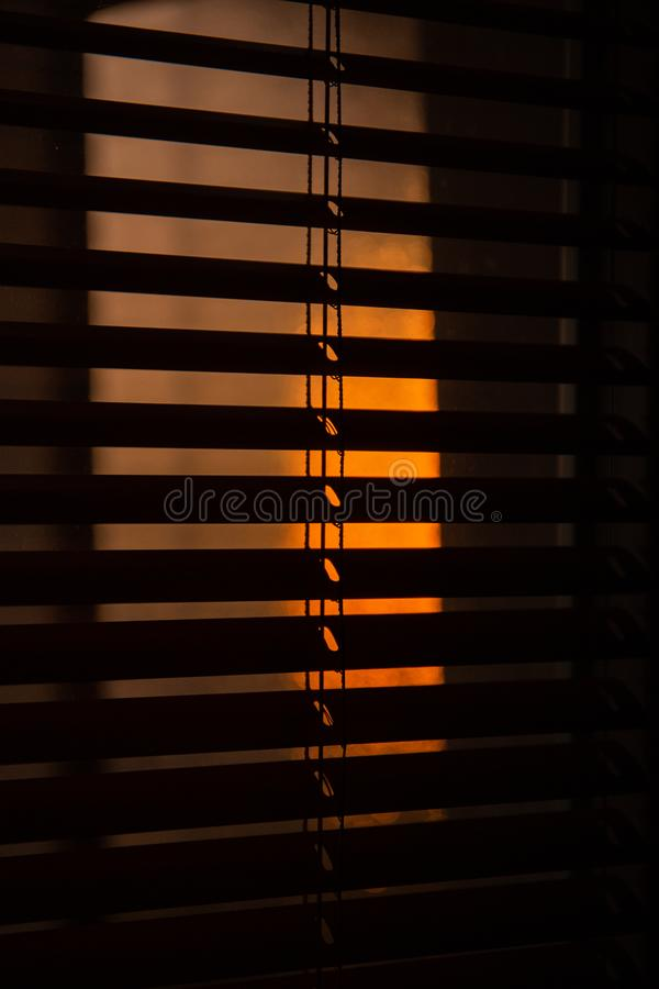 Sun filtering through venetian shades; indoor, golden sunset light.  stock photography