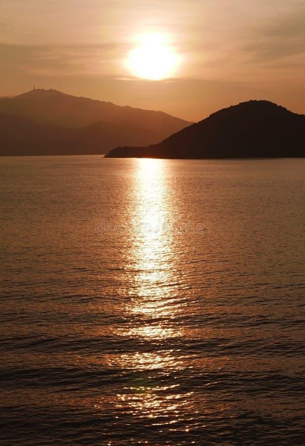 Sun-, Gebirgs-, Ozean- und Wasserwelle bei Sonnenuntergang stockfoto