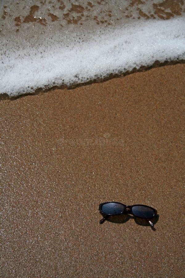 Sun-Gläser im Sand am Strand lizenzfreie stockfotos