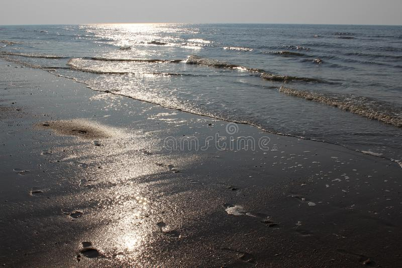 Sun glare on the waves of the North Sea at sunset. Footprints in the wet sand and evening sky. Ostend, Belgium. Sun glare on the waves of the North Sea at sunset royalty free stock images