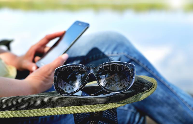 Sun glasses lie on the armrest of the lounge chair, the girl in the armchair looks at a mobile phone against the background of royalty free stock images