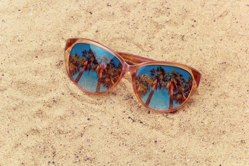 Sun glasses with palms reflection on the beach stock image