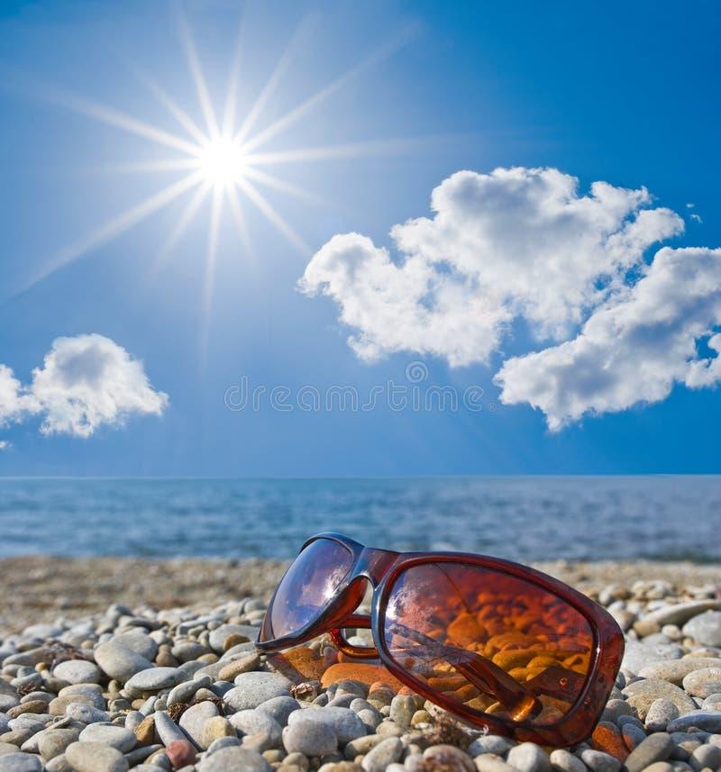 Sun glasses on a seashore royalty free stock image
