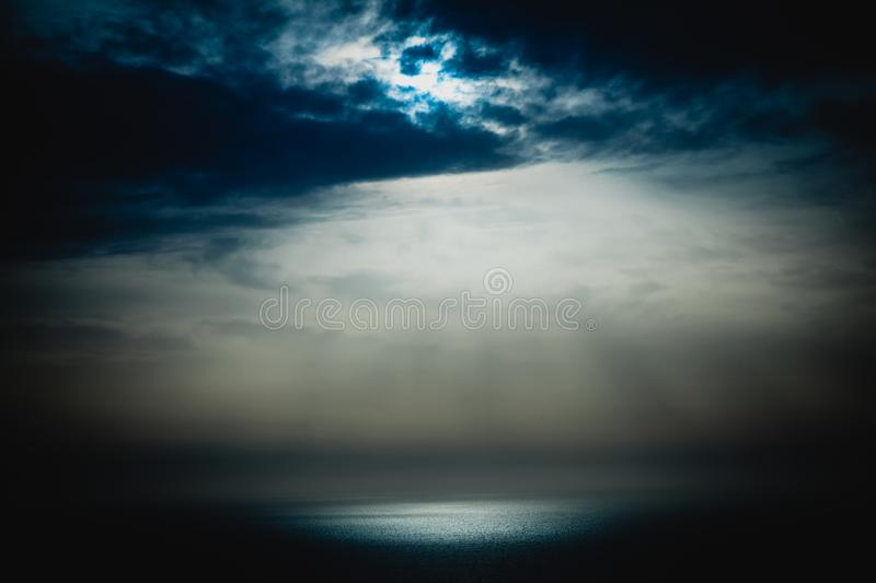 Sun going through the clouds at the end of the day stock photography