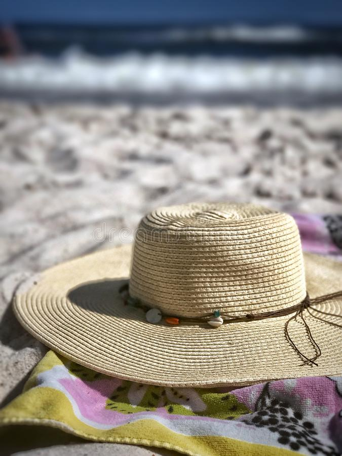Sun Hat on the Beach. A sun hat tossed aside on a towel on the sand with the ocean waves in the background stock photography