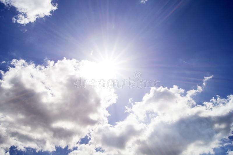 Sun hidden behind light gray clouds against the blue sky royalty free stock photo
