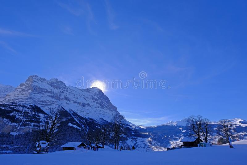 The sun hides behind the famous peak of the Eiger mountain above Grindelwald, with a lot of snow, Bern, Switzerland stock image