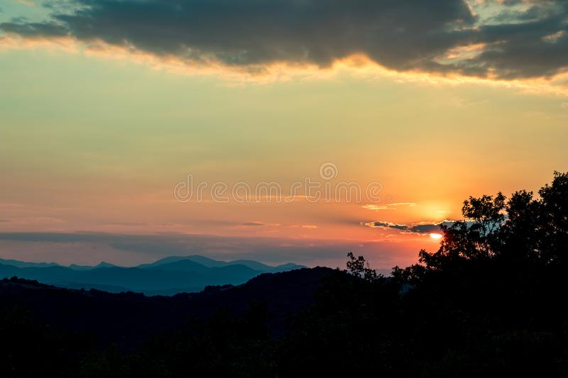 Sun hiding behind clouds colorful summer sunset royalty free stock photos