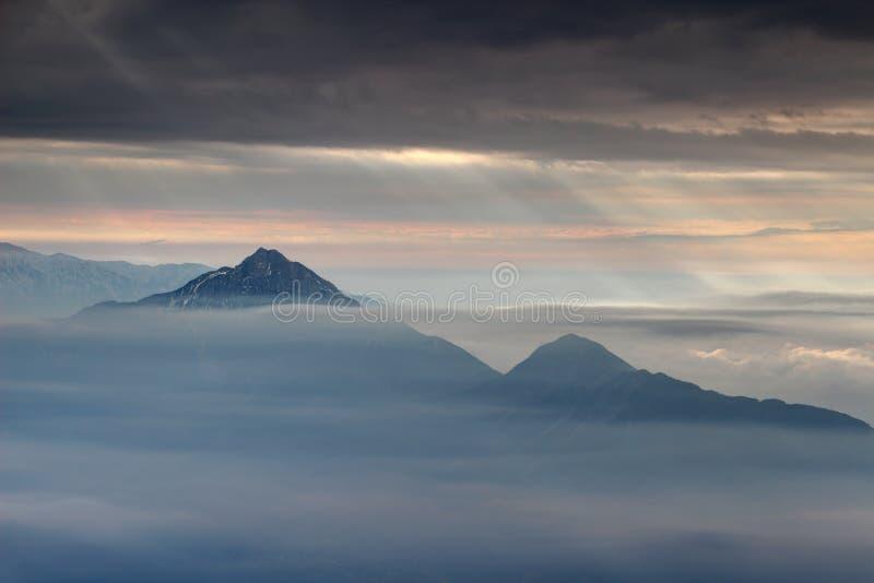 Sun irradia a explosão através das nuvens escuras sobre picos na névoa do outono imagem de stock