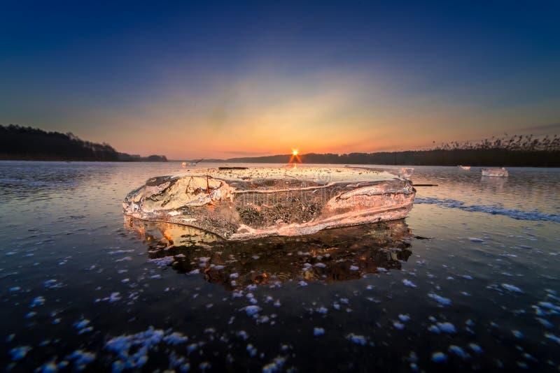 Sun irradia iluminando un pedazo de hielo en el lago imagen de archivo